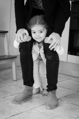 fillette accrochées aux jambes de sa maman