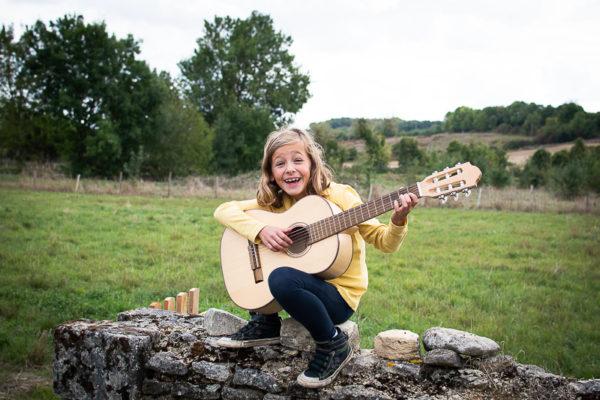 Enfant et sa guitare dans son jardin