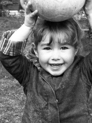 Petite Fille qui tient un ballon sur sa tête