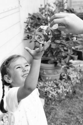 petite fille qui cueille une bulle de savon