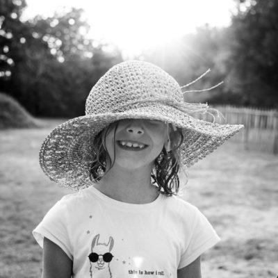 enfant avec chapeau de sa mère sur la tête. NB