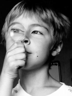 Garçon tenant devant son oeil une loupe. NB