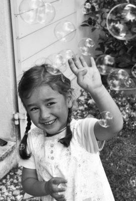 fillette qui se protège en riant nuage de bulles de savon